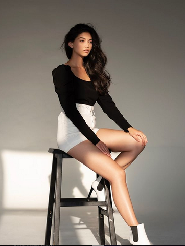 Brown-haired woman sitting on stool